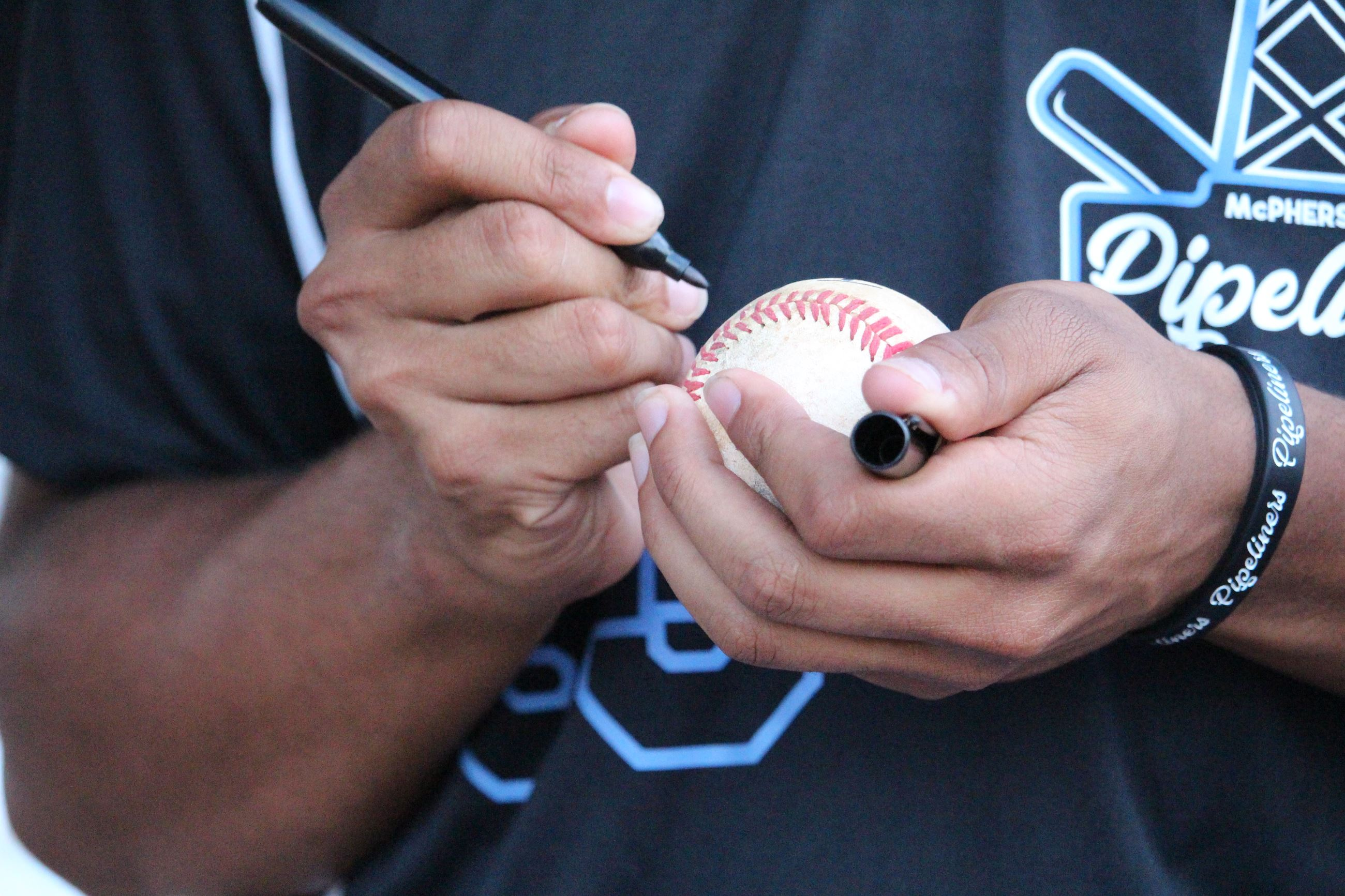 Closeup of baseball player holding a baseball and pen during a signing session