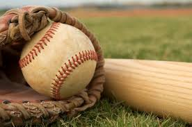 Baseball, baseball mitt and baseball batt laying on a baseball field