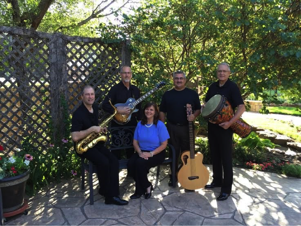 Five gospel musicians sit with their instruments in an outdoor setting