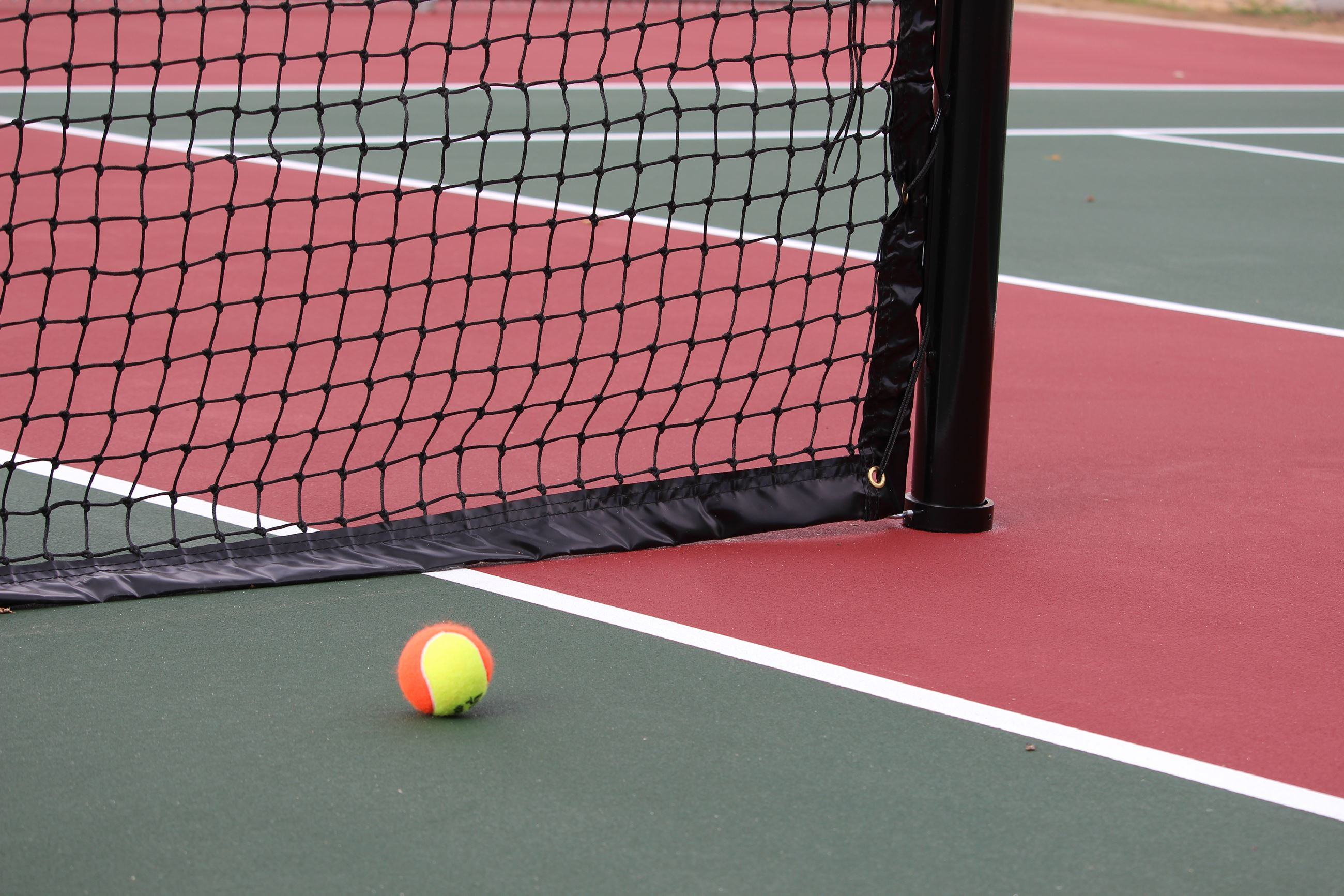 A tennis ball sitting on the court next to the net