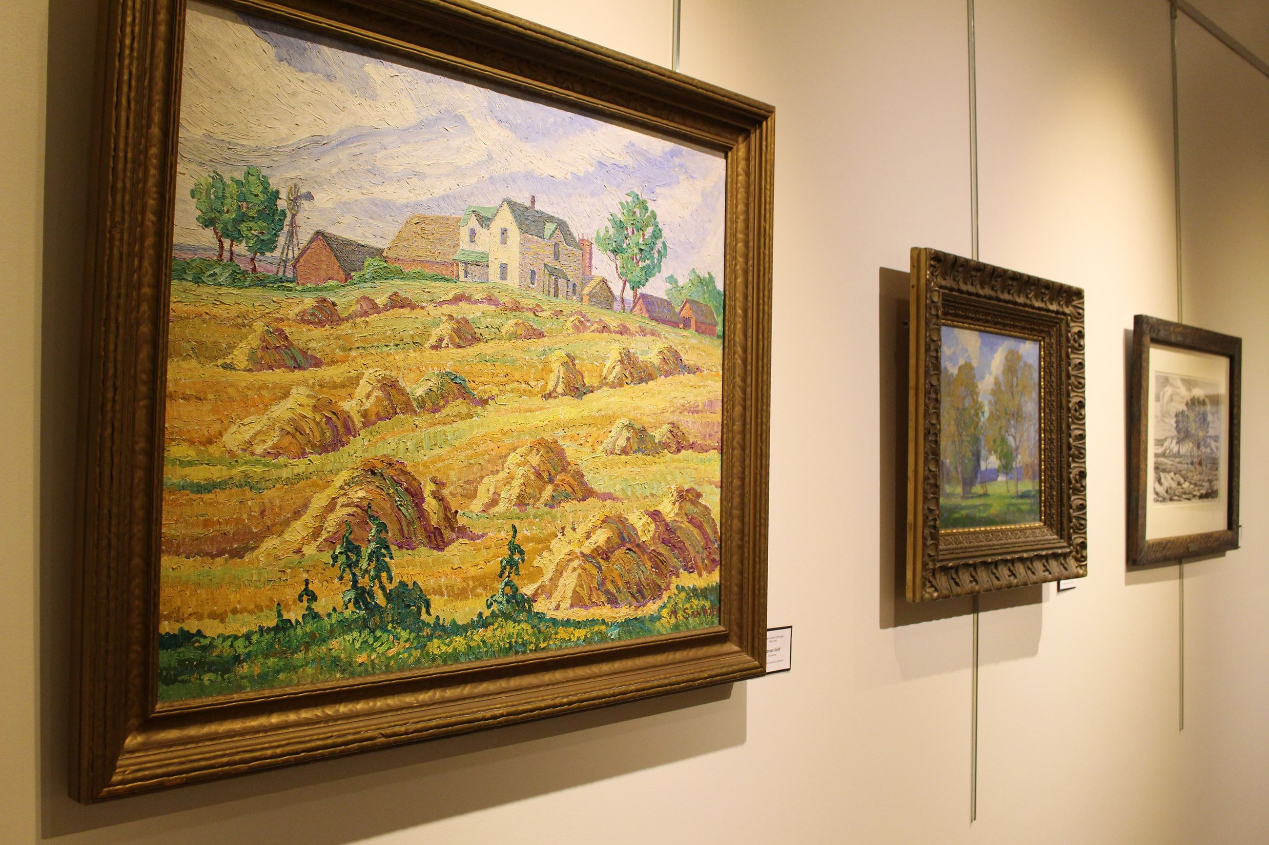 Three paintings hang on a wall at the McPherson Museum